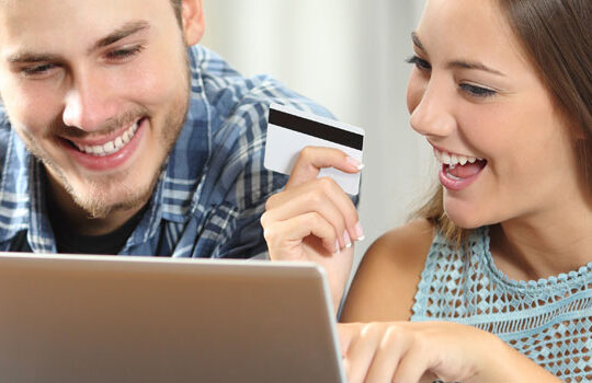 Couple looking at laptop with credit card in hand